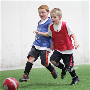 two kids playing in lil' kickers and skills institute class