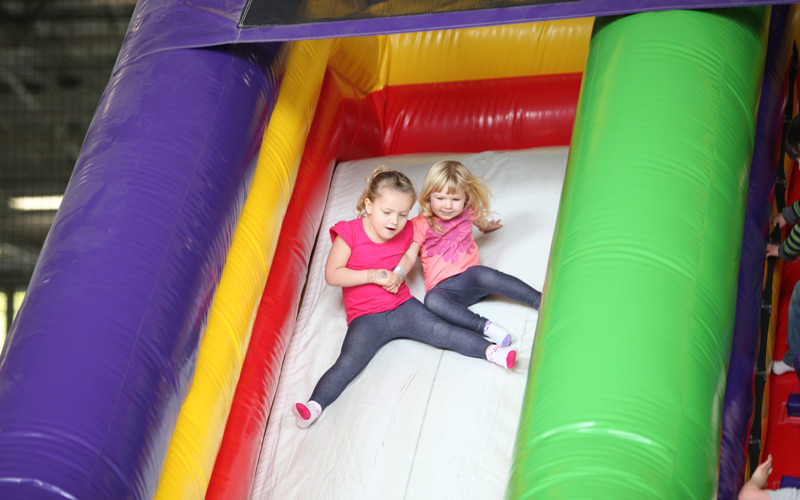 two girls sliding down funzone slide.