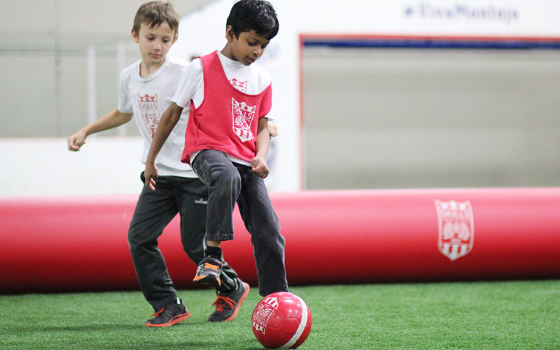 Skills Institute Boys Playing with a Red Soccer Ball